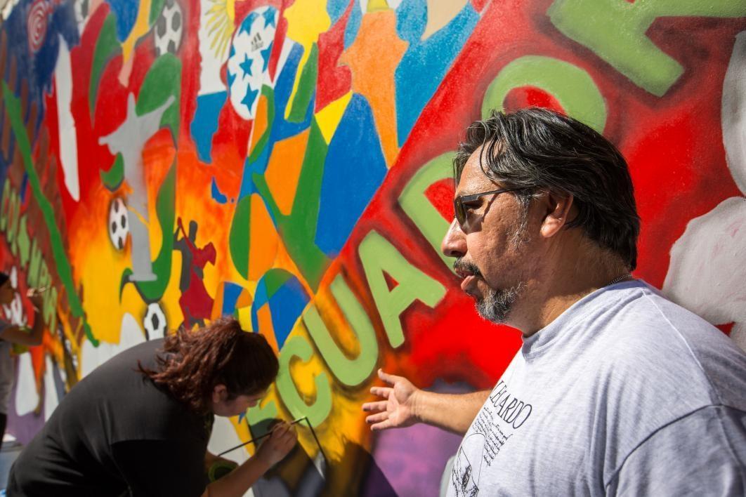 artist Hugo Medina standing in front of mural