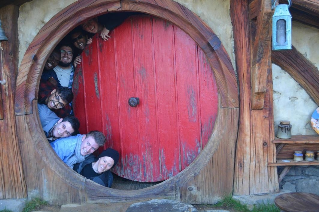 students pose in Hobbiton in New Zealand