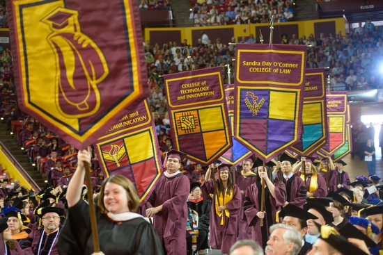 ASU graduate standing up in crowd to wave during graduate commencement