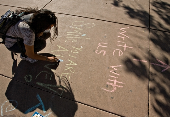 student writing on sidewalk