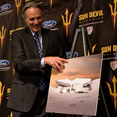 man unveiling poster of stadium rendering
