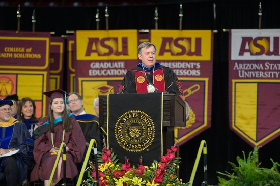 two ASU graduates high fiving during graduate commencement