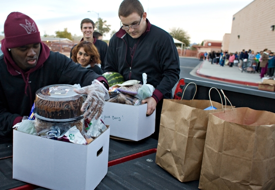 football players help load food