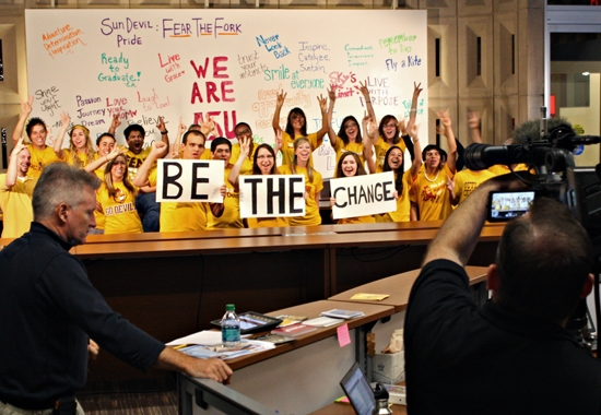 students holding up signs that say BE THE CHANGE