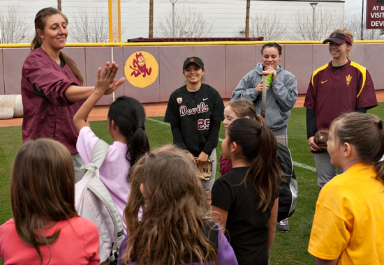 softball player meeting with kids