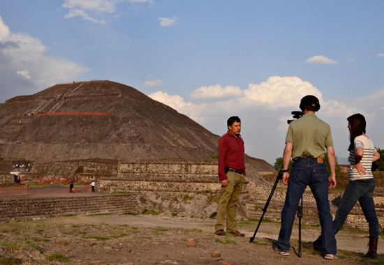 people filiming man in front of pyramid