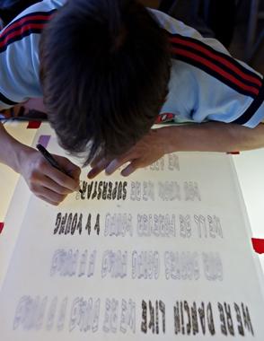 student artist working on stencil