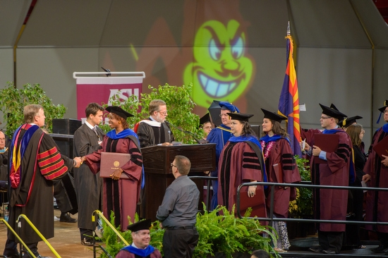 graduates lined up on stage to shake ASU President Crow's hand