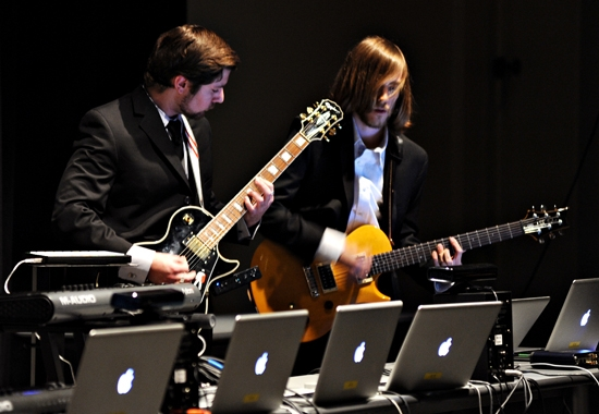people playing guitars with laptops