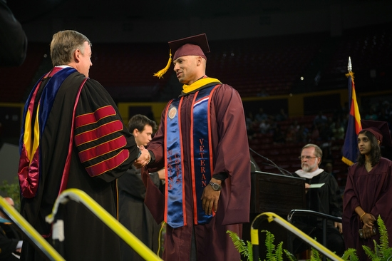 ASU President Crow shaking hands w/ veteran during graduate commencement