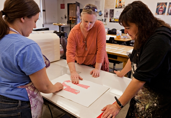 students and professor working on art piece