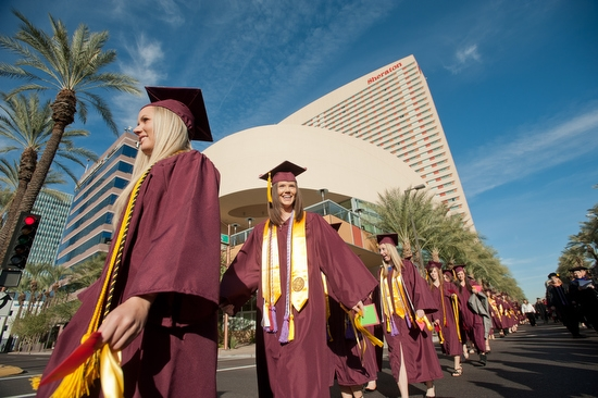 students walking in downtown Phoenix in caps and gowns