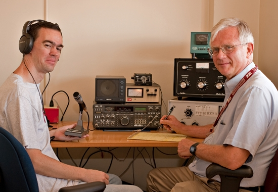 two men sitting in front of radio equipment