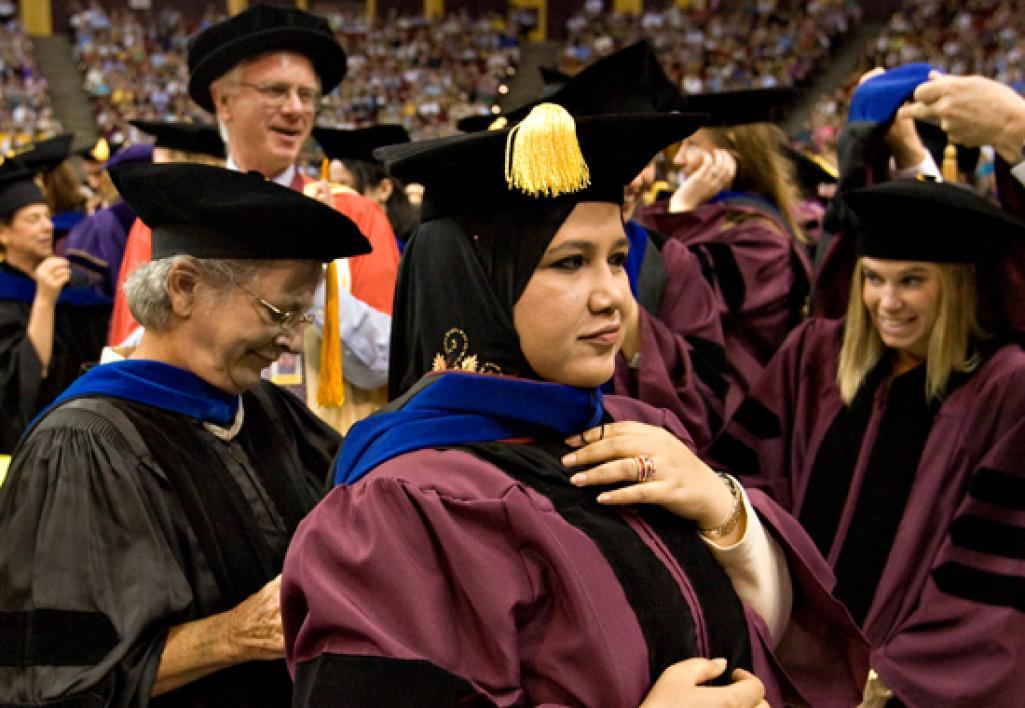 professor placing doctoral hood on student