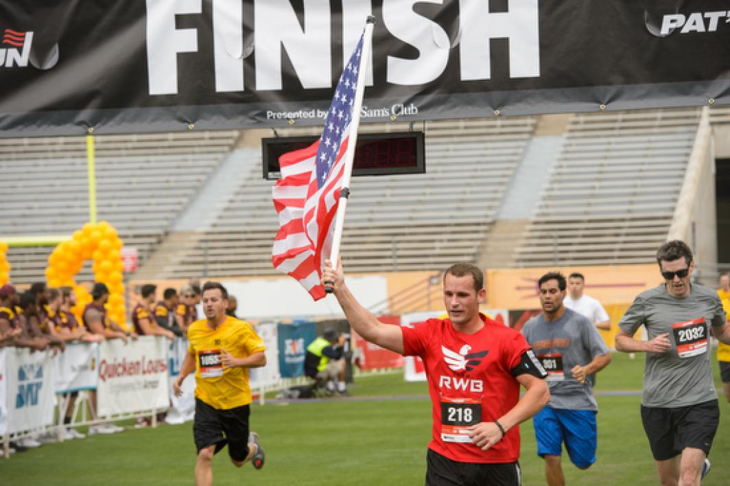 man holding American flag crosses finish line
