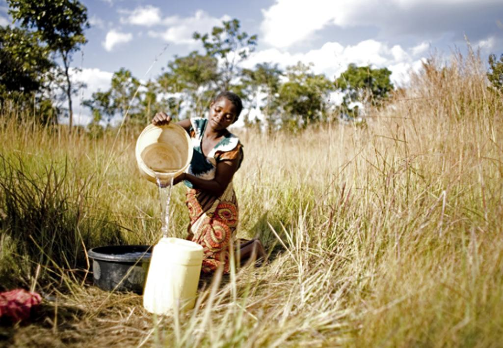 Girl collects water from well.