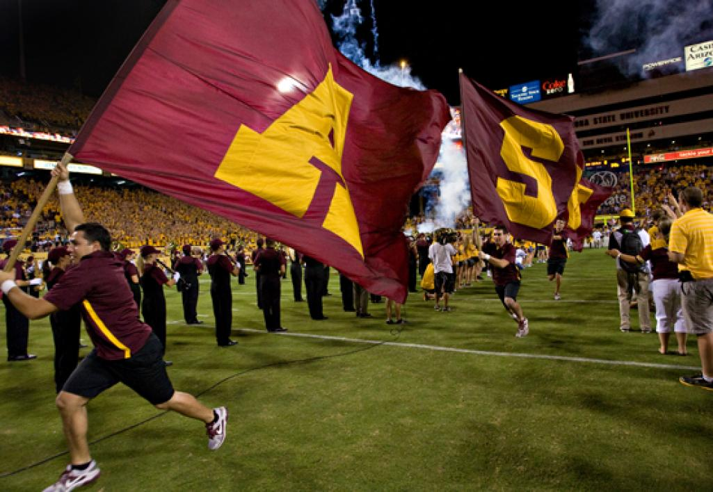 people carrying ASU flags on to football field