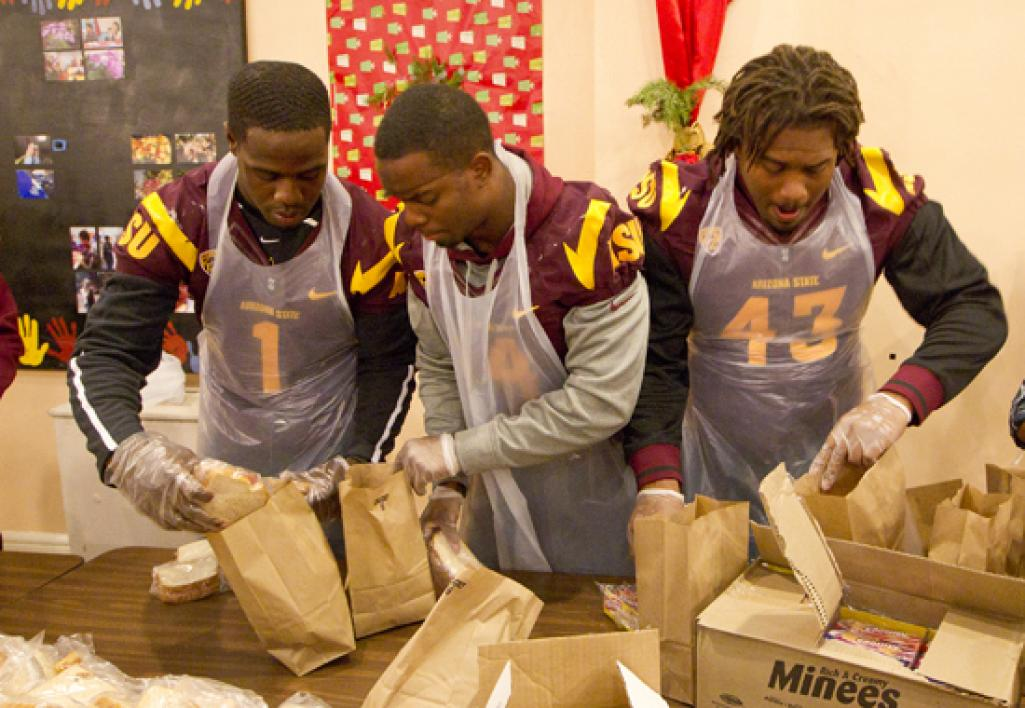 football team volunteers in food kitchen