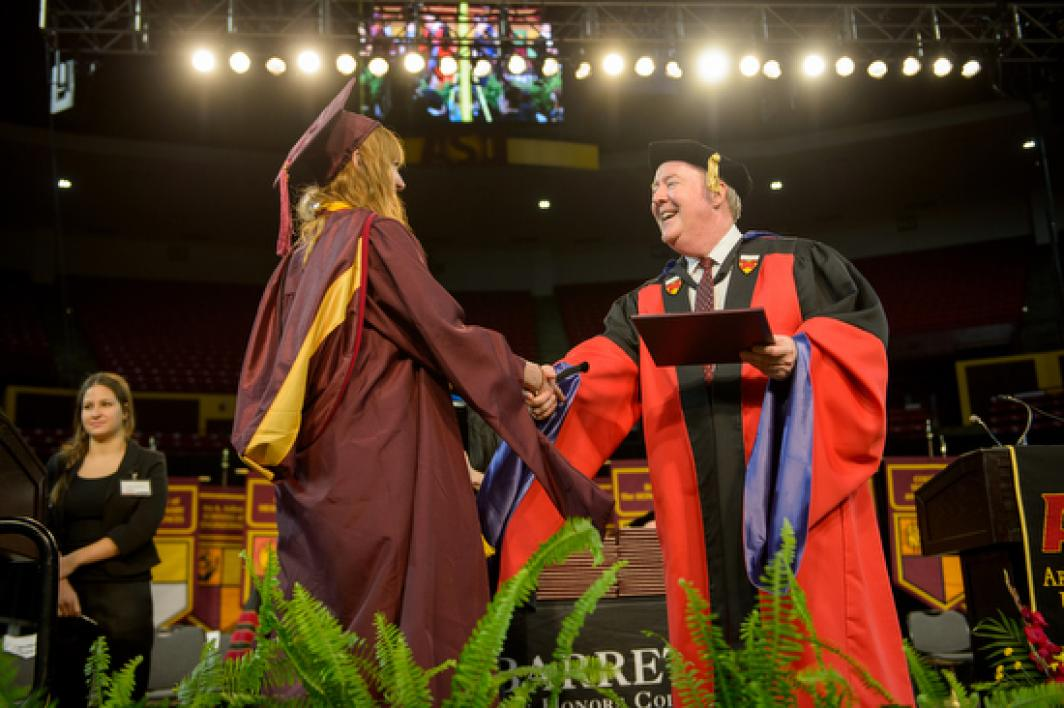 Barrett dean Mark Jacobs shaking hands with graduate during convocation