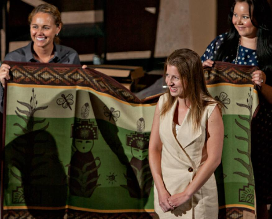 graduate participating in blanket wrapping ceremony
