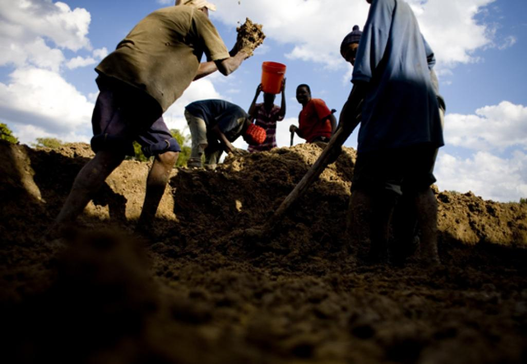 Men scrape up soil for bricks.