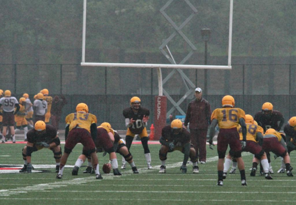 football team practicing in the rain