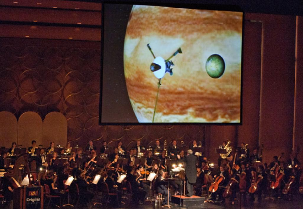 orchestra playing in front of screen with Jupiter on it