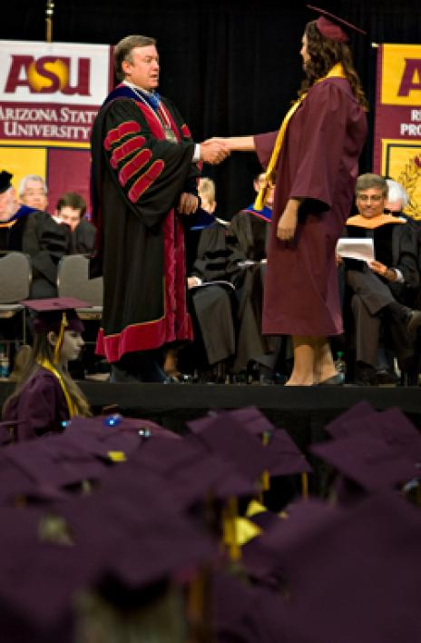 woman in cap and gown shaking hands with university president