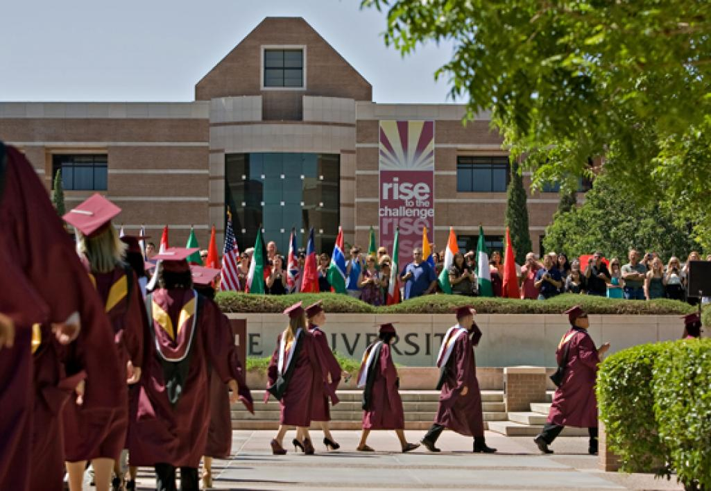 students walking on campus in caps and gowns