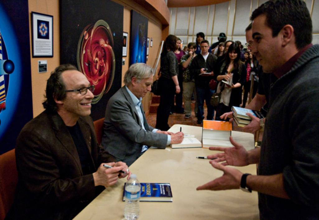 men signing books