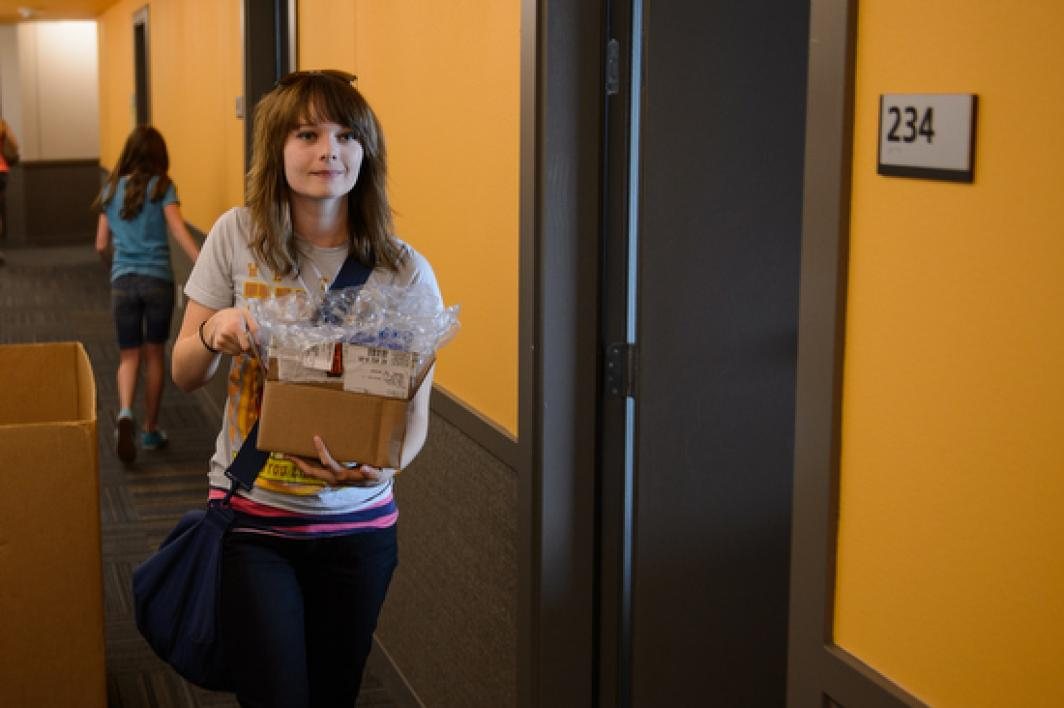 student carrying items down hallway of Manzanita Hall