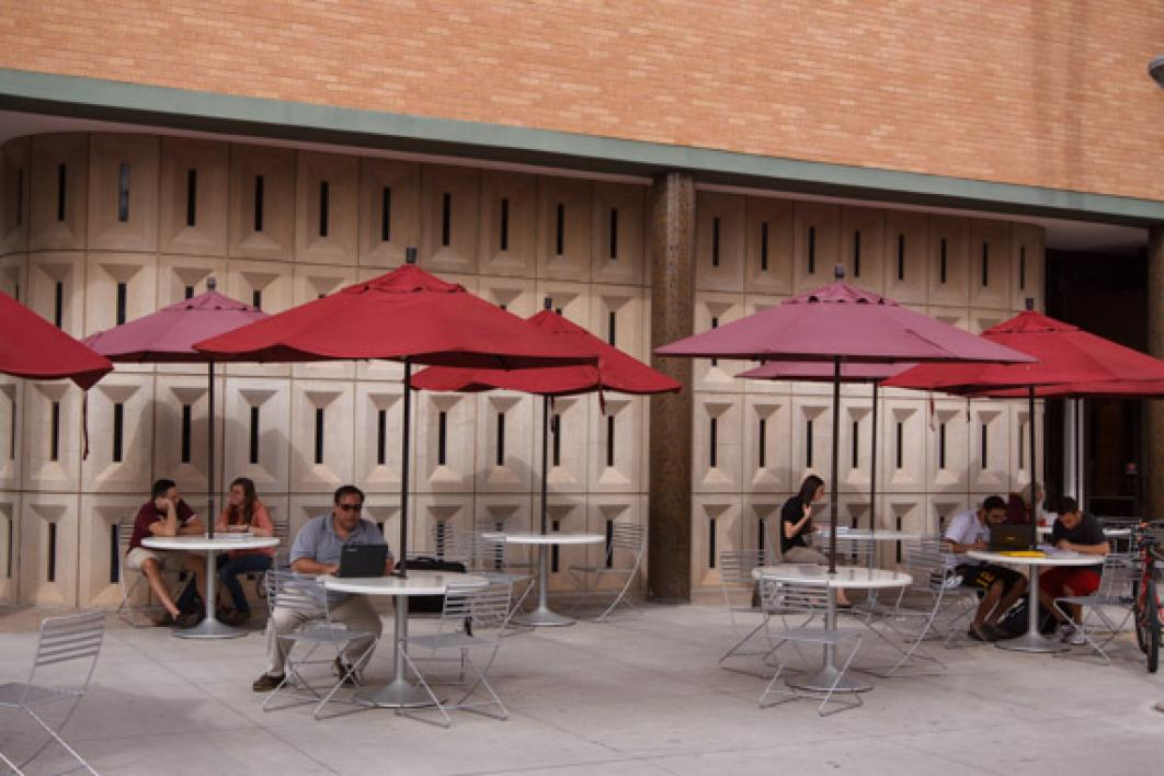 students sitting at tables on campus