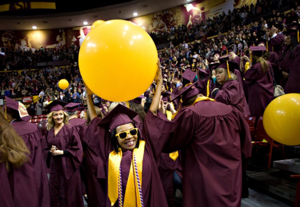 woman in cap and gown holding balloon over head