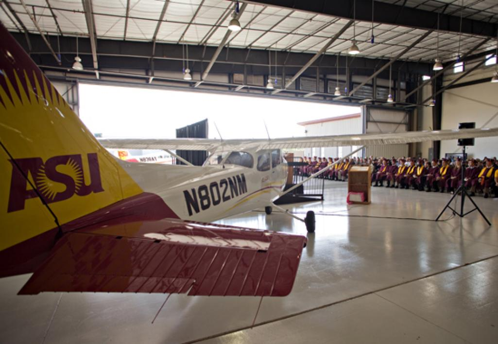 plane inside aviation hanger in front of graduates