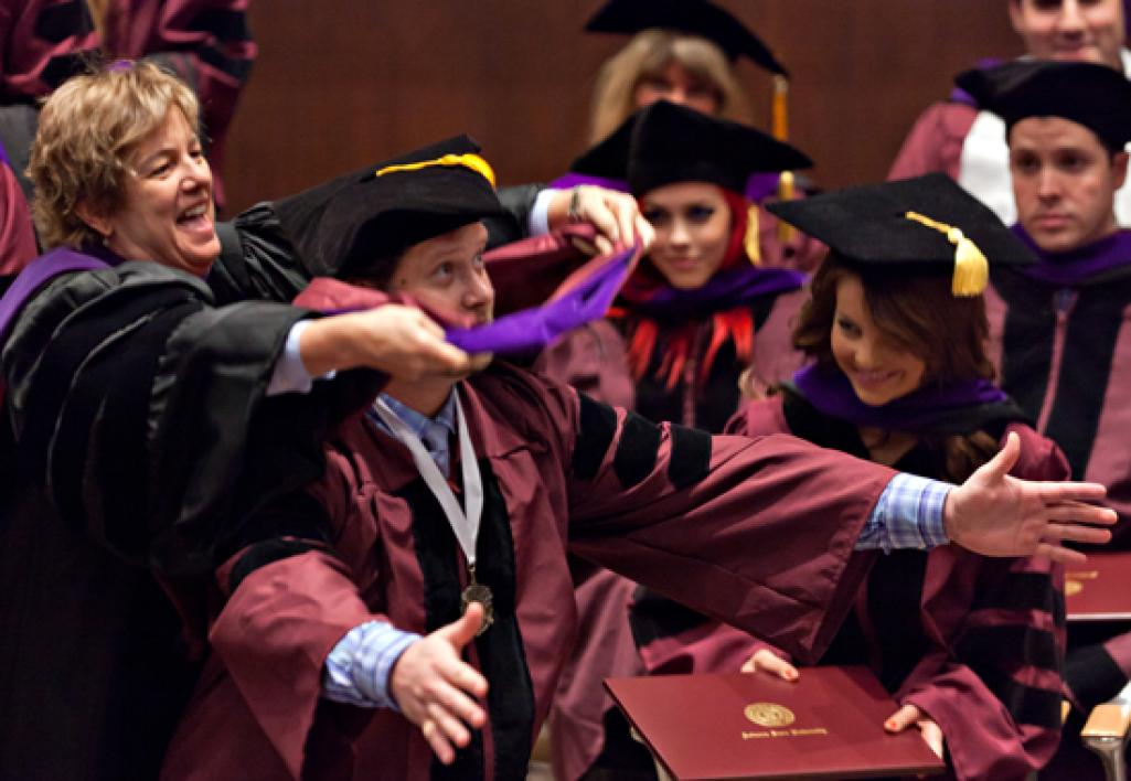 professor placing doctoral hood on student