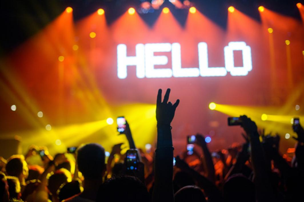 student's hand flashing pitchfork sign during concert