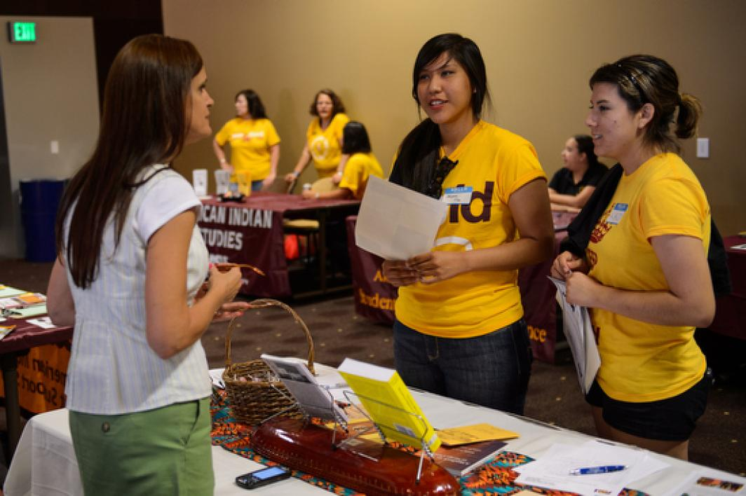 students talking to person at booth