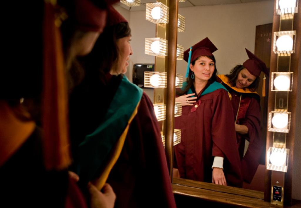 woman helping graduate with robe