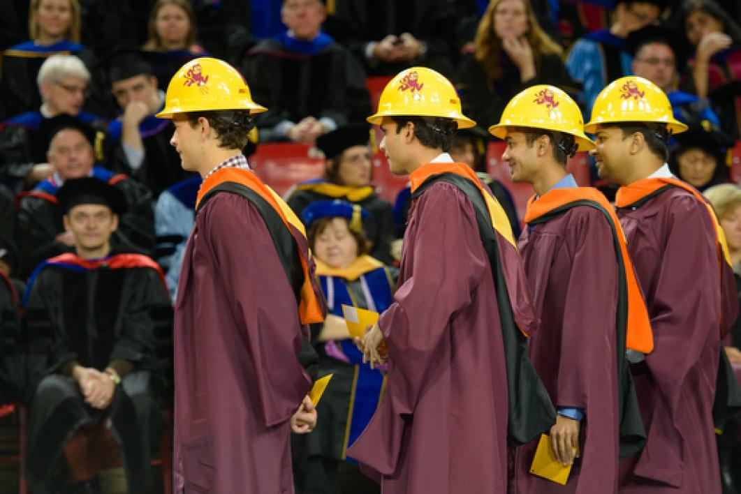 construction students in hardhats walking to stage