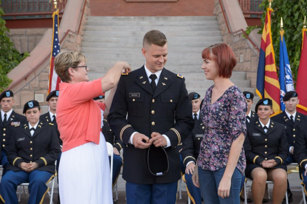 mother pinning son's military jacket