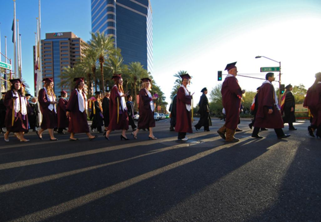 students in caps and gowns crossing street