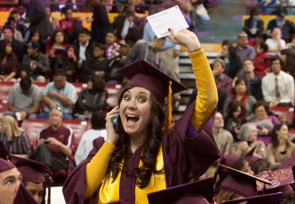student waving at graduation