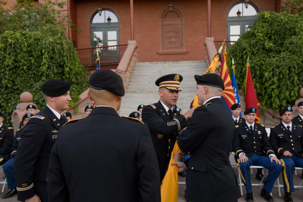 lieutenant colonel handing flag to cadet