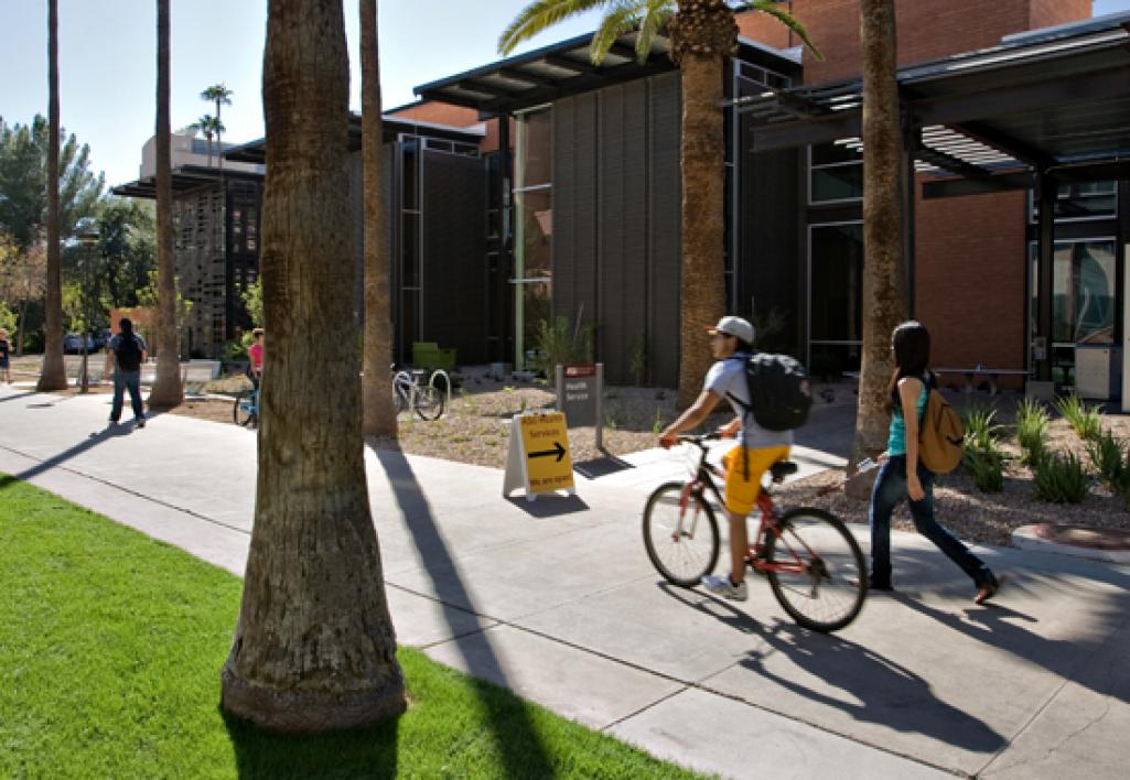 people riding bike past building