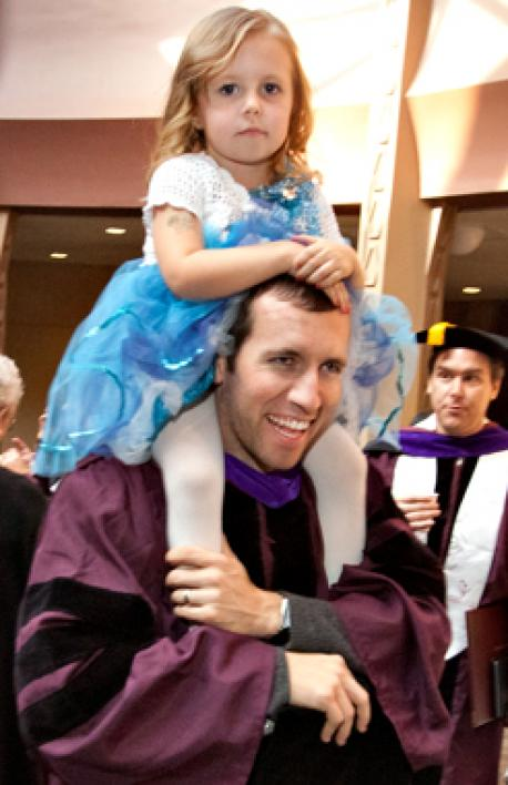 man holding daughter on his shoulders