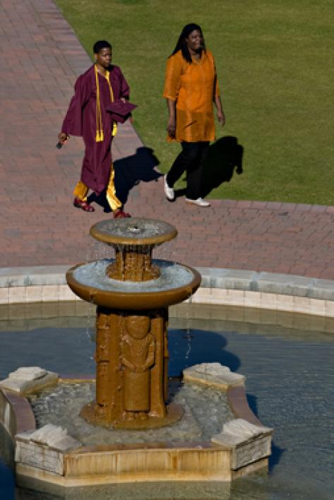 two women walking past fountain