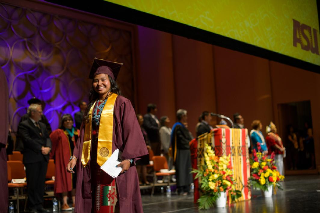 graduate walking out on stage during ASU American Indian Convocation