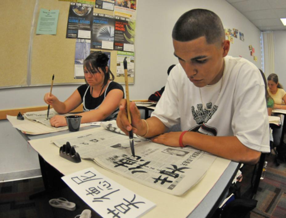 student painting Chinese symbols