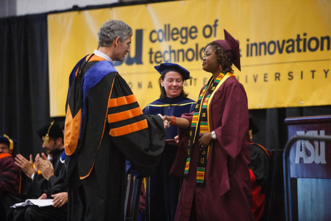 dean shaking hands with grad during ASU CTI convocation