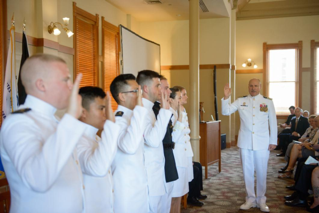ensigns saluting during ASU Navy ROTC commissioning ceremony